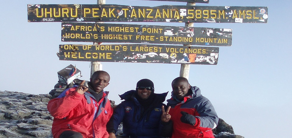 Wanderlust-founder-on-one-of-his-many-summits-on-Kilimanjaro-flanked-by-two-Tanzanian-guides
